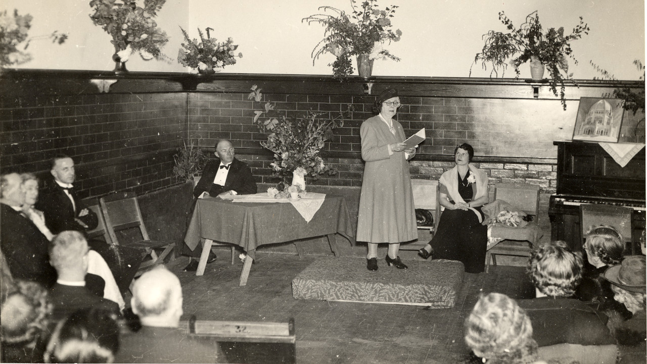 People in formal attire seated around the room watching Clara Dunn reading from a small book