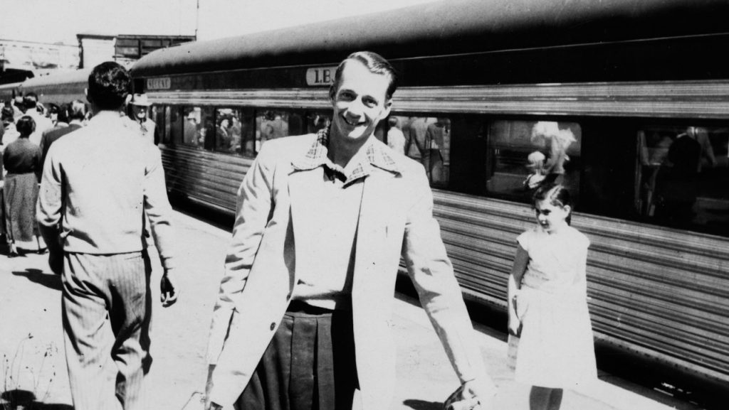 Smiling man holding suitcase in front of train with passengers behind him